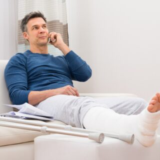 Man with cast on his leg sat on the phone