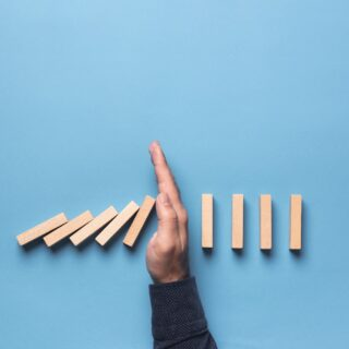 Hand stopping falling dominoes to illustrate the theme of business insolvency.